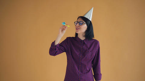 Playful young woman in birthday hat is blowing party horn dancing having fun Footage