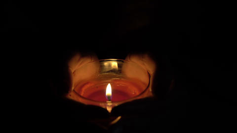 footage burning candle in the hands of women. 4K Footage