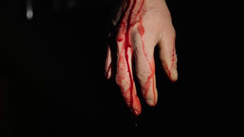Bloody male hand with blood dripping on the dark background Footage