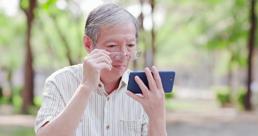 Older man watch video by cellphone Live Action