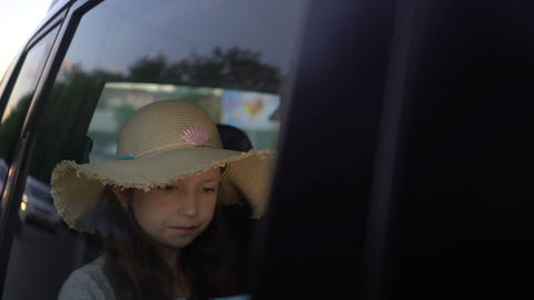 happy little girl with computer tablet driving in car backseat. road trip Live Action