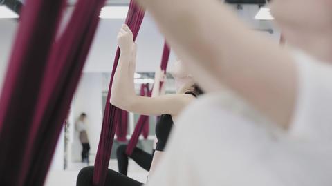 Anti-gravity Yoga, women doing yoga exercises indoor Stock Video Footage