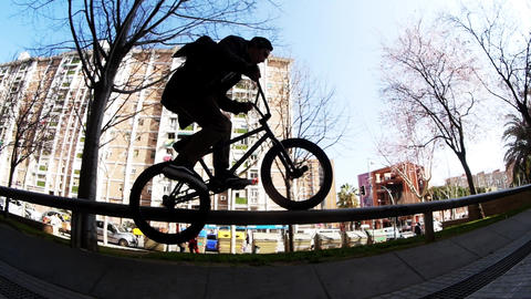 Extremal bicycler rides and jumps on his bike on silver metallic handrails Footage