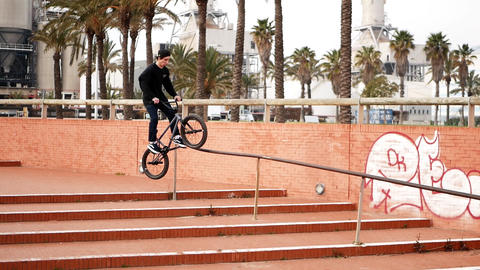 Nice looking guy rides on bike and jumps over cascade brick stairs and handrails Footage