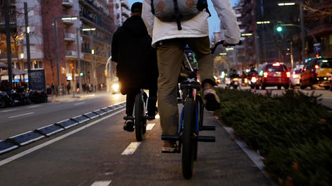 Young men cyclists are riding along narrow road with cars in big busy night city Footage