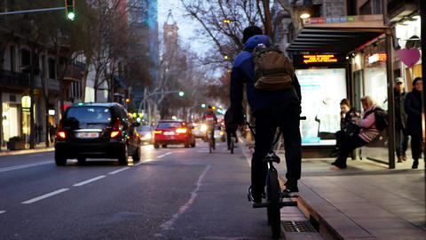 Slim small guy bmx rider moves along road with cars in big busy night city Live Action