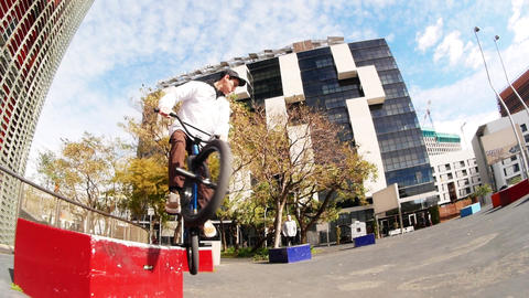 Sportive skilled man BMX rider practices flips and spins on bike in urban area Live Action