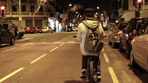 Young male cyclist is carefully riding along narrow road with cars in night city Live Action