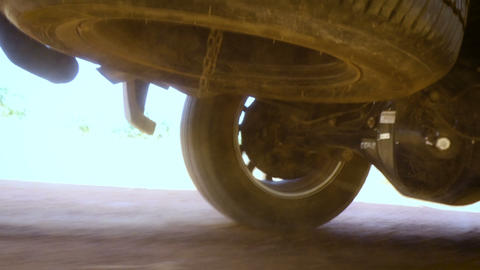 Rear wheel of SUV truck spinning and move on off road terrain with dusk dirty earth and blurry shake Live Action