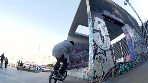 Guy BMX biker makes different spins and tricks on bike in urban environment Live Action
