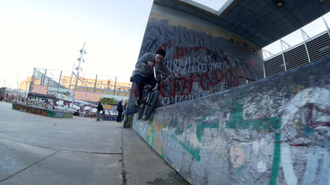 Cool BMX rider makes lots of spins and tricks on bike next to wall with graffiti Footage
