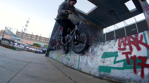 Teen BMX rider makes different spins and tricks on bike in urban environment Live Action