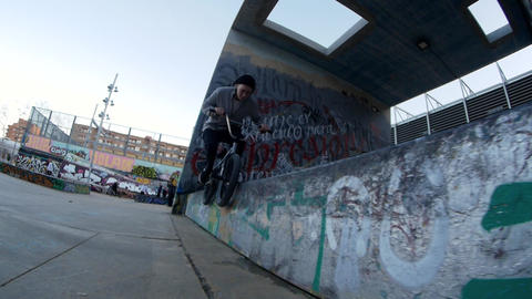 Active BMX rider makes different spins and tricks on bike in urban environment Footage