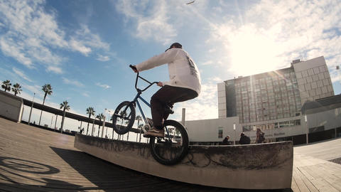 Skilled male BMX rider practices flips, jumps and spins on bike in urban area Live Action