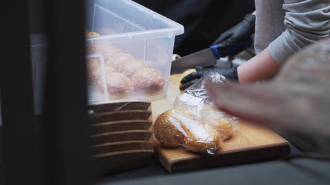 Someone technically cuts sesame seed buns to halves on wooden board Live Action