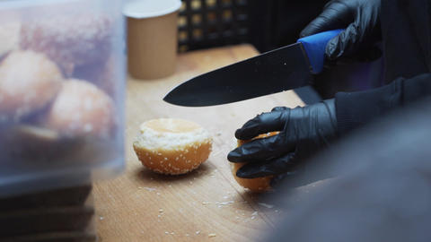 Someone wearing black gloves cuts sesame seed buns to halves on wooden board Live Action