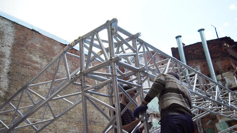 Two mature male workers are setting grey metallic stage structure outside Footage