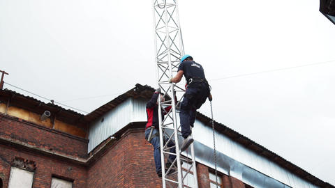Two men wearing scaffolding safety uniform with helmets climb up on PA tower Footage
