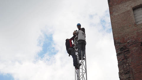 Mature men wearing dark casual clothes and helmet works at top of PA tower Footage