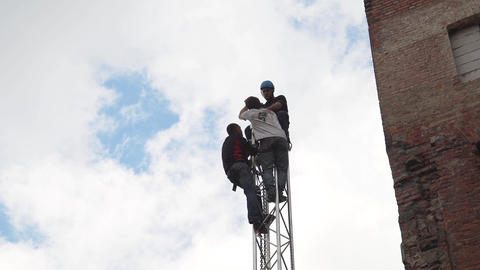 Three men dressed in casual clothes and helmet are working at top of PA tower Footage
