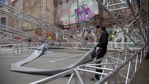 Two young men are mounting grey tarpaulin dome onto metallic stage structure Footage