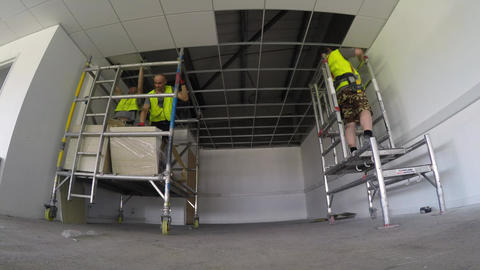 Construction, installing ceiling tiles to the grid in small area Live Action