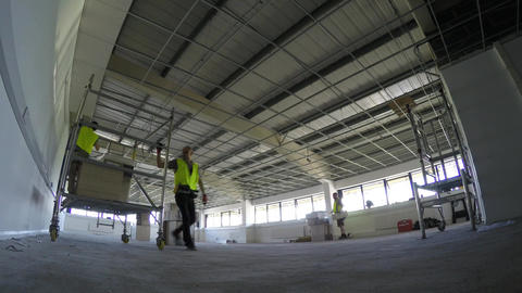 Construction, installing ceiling tiles to the grid in large area Live Action