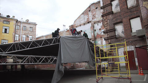 Men workers are covering aluminium stage structure with grey opaque tarpaulin Footage