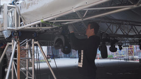 Young man in black t-shirt mounts equipment to constructions of stage under dome Footage