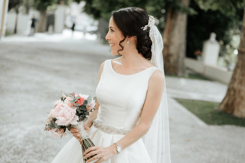 Smiling beautiful young bride in wedding dress with bouquet of flowers Photo