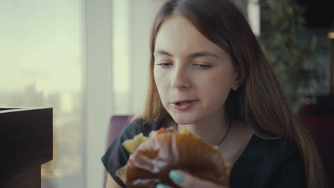 Footage young woman eating tasty burger in fast food restaurant Footage