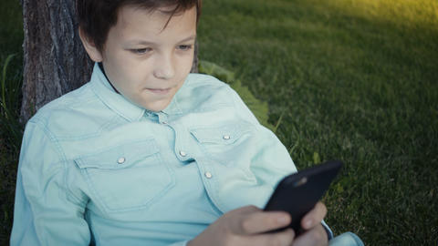teenager playing video games on his smartphone outdoors Footage