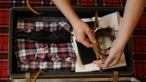 [alt video] Man hands packing suitcase for travel. Top view. Flannel...