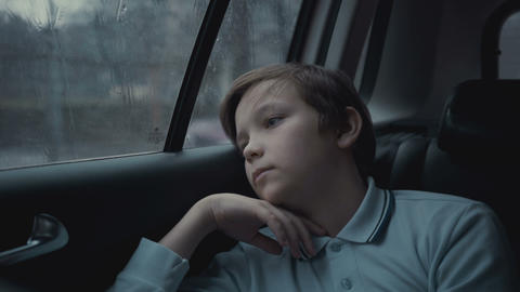 Sad, unhappy young boy riding in car through city during rainy day Footage