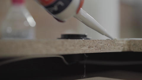 The worker putting silicone glue on the MDF board close up. Profession of the Footage