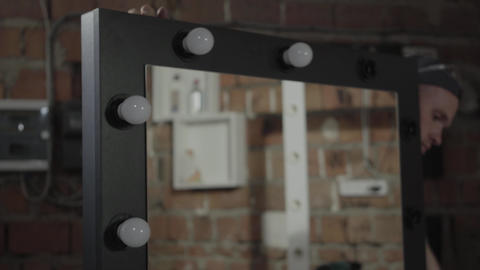 Close up of the electrician screwing light bulbs in the mirror. Concept of hand Footage