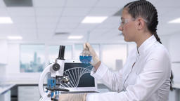 Female laboratory assistant examines a cure for cancer. A female scientist is Footage
