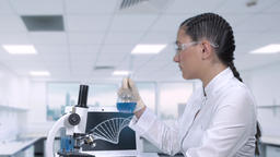 A female lab technician is researching a cure for cancer. A female scientist is Footage