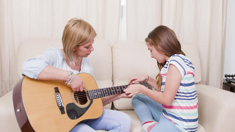 Mother and daughter in the living room learning to play on an acoustic guitar GIF