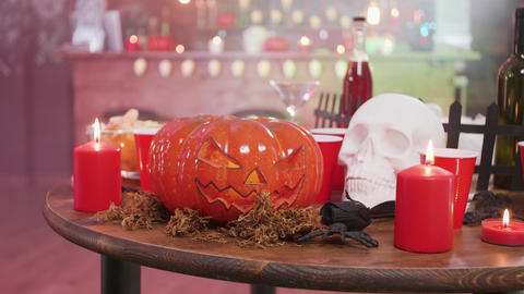 Jack-o-lantern halloween symbol on a table with a skull and candles GIF