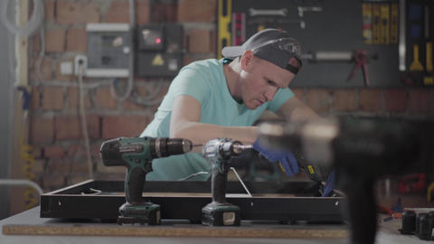 The carpenter in black cap and gloves putting glue on the wooden frame. The man Footage
