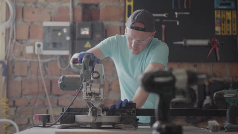 Portrait craftsman in protection glasses cutting a wooden board with a small Footage