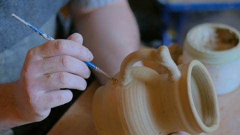 Professional male potter working in workshop, studio GIF