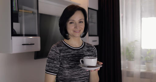 Portrait of pretty young brunette woman smiling and drinking coffee from cup Footage
