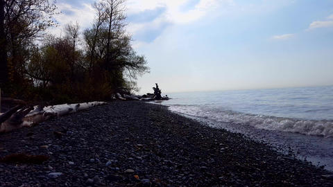 Small Breaking Waves on Beautiful Rocky Beach Shore. Daytime Vacation Shoreline Beach Destination in Live Action
