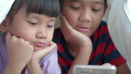 Asian children's brother and sister using tablet under the blanket on the bed, closeup Archivo
