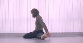Tender caucasian professional ballerina warming up making leg-split in light Footage