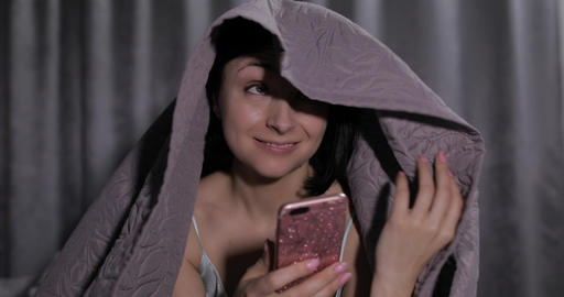 Woman sitting on bed under blanket and enjoying chatting to friend on smartphone Footage