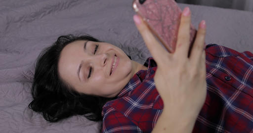 Woman lying on bed and using smartphone for enjoying chatting to friend Live Action
