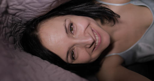 Woman sitting on bed under blanket. Enjoying video chat to friend on smartphone Footage